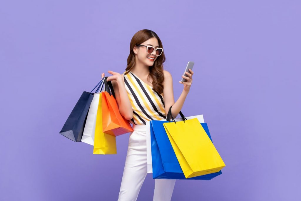 beautiful-asian-woman-carrying-colorful-bags-shopping-online-with-mobile-phone