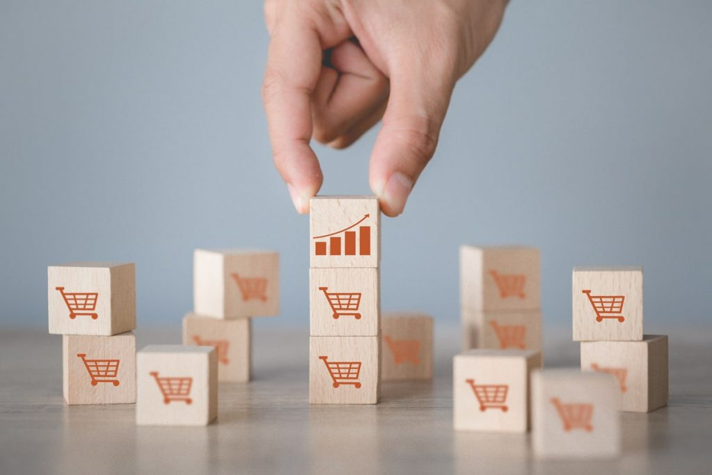 hand-arranging-wood-block-stacking-with-icon-graph-shopping-cart-symbol-upward-direction