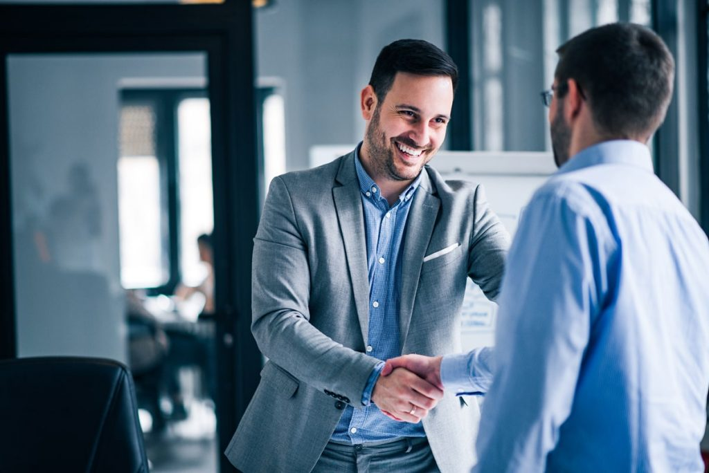 two-smiling-businessmen-shaking-hands-while-standing-office